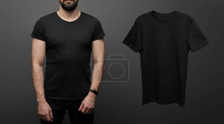 Photo for Cropped view of bearded man near blank basic black t-shirt on black background - Royalty Free Image