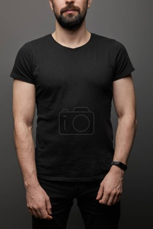 Photo for Cropped view of bearded man in blank basic black t-shirt on black background - Royalty Free Image
