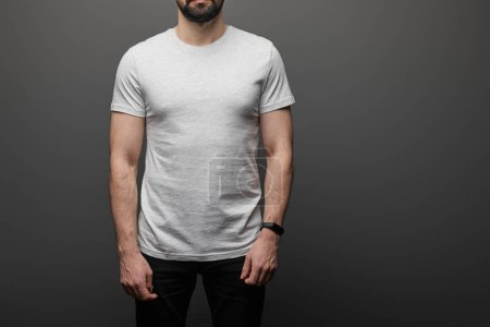 Photo for Cropped view of bearded man in blank basic grey t-shirt on black background - Royalty Free Image