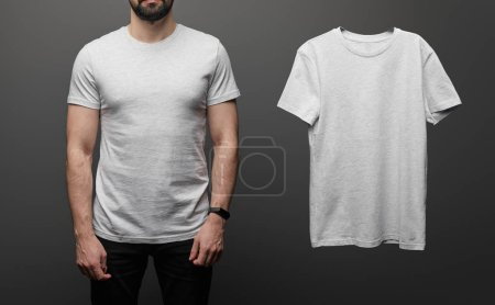 Photo for Cropped view of bearded man near blank basic grey t-shirt on black background - Royalty Free Image