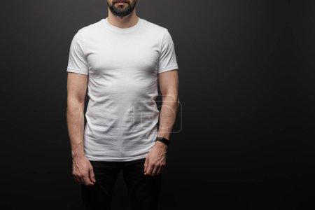 Photo pour Crochet d'un homme barbu en T-shirt blanc de base en blanc isolé sur noir - image libre de droit