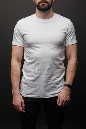 Foto de Vista del hombre portador con camiseta blanca en blanco y en blanco aislada sobre negro. - Imagen libre de derechos