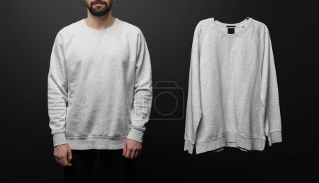 cropped view of bearded man near blank basic grey sweatshirt isolated on black