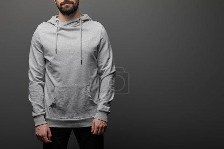 Photo pour Vue recadrée de l'homme barbu en blanc capuche gris de base sur fond noir - image libre de droit