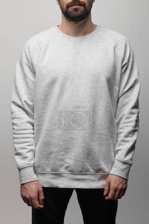 Photo pour Vue recadrée de l'homme barbu en sweat blanc gris basique isolé sur gris - image libre de droit