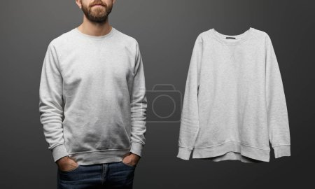 cropped view of bearded man near blank basic grey sweatshirt on black background