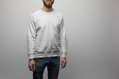 partial view of bearded man in blank basic grey sweatshirt isolated on grey