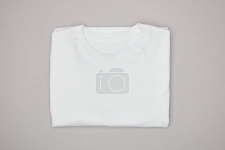 top view of blank basic white t-shirt isolated on grey