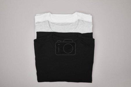 Photo pour Vue du dessus des t-shirts blancs, blancs et gris isolés sur gris - image libre de droit
