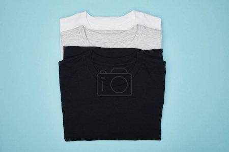 Photo for Top view of blank basic black, white and grey t-shirts isolated on blue - Royalty Free Image