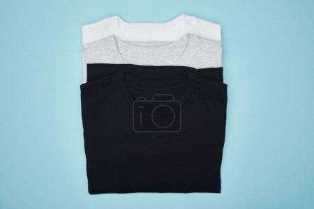 Photo pour Vue du dessus des t-shirts blancs, blancs et gris isolés sur bleu - image libre de droit