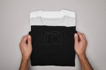 Photo pour Vue recadrée de l'homme touchant des t-shirts noirs, blancs et gris vierges isolés sur gris - image libre de droit
