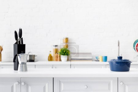 Photo for Modern white kitchen interior with coffee pot, pot and knives on table - Royalty Free Image