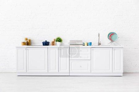 Photo pour Cuisine blanche moderne intérieure avec ustensiles de cuisine près du mur de brique - image libre de droit