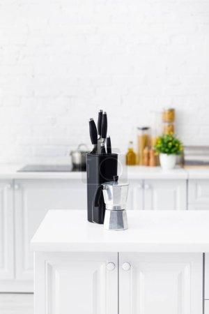 Photo pour Intérieur moderne de cuisine blanche avec cafetière et couteaux sur la table - image libre de droit