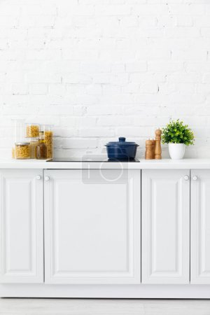Photo for Modern white kitchen interior with pot on electric induction cooktop near decor and food containers near brick wall - Royalty Free Image
