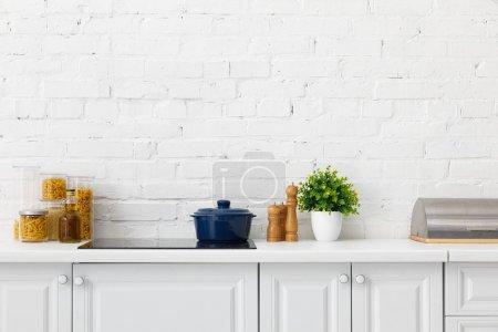 Photo pour Cuisine blanche moderne intérieur avec pot à induction électrique table de cuisson près de l'usine et contenants d'aliments près du mur de brique - image libre de droit