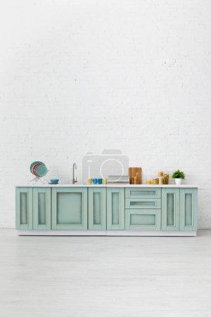Photo pour Cuisine moderne blanche et turquoise intérieur avec ustensiles de cuisine près du mur de brique - image libre de droit