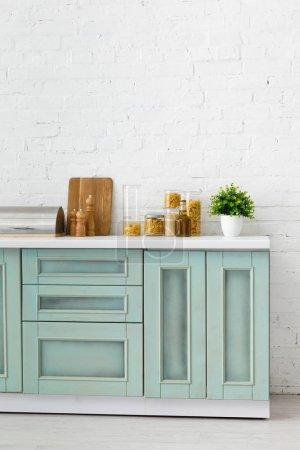 Photo pour Cuisine moderne de couleur blanche et turquoise avec ustensiles de cuisine, récipients pour aliments et plantes près d'un mur de briques - image libre de droit