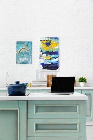 Photo pour Mise au point sélective d'un ordinateur portable et d'une casserole à induction avec ustensiles de cuisine et peintures abstraites à l'arrière-plan - image libre de droit