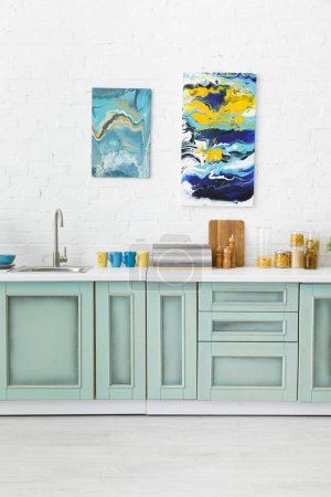 Photo for Modern white and turquoise kitchen interior with kitchenware and abstract paintings on brick wall - Royalty Free Image