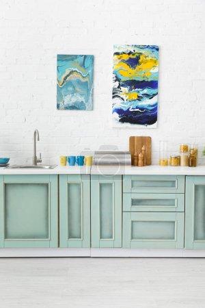 Photo pour Intérieur de cuisine moderne blanc et turquoise avec ustensiles de cuisine et peintures abstraites sur mur de brique - image libre de droit