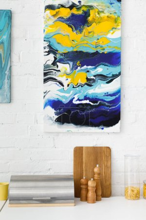 Foto de Cocina moderna, blanca y turquesa, con menaje y pintura abstracta en la pared de ladrillo. - Imagen libre de derechos