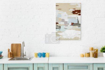 Photo pour Intérieur de cuisine moderne blanc et turquoise avec ustensiles de cuisine et peinture abstraite sur mur de brique - image libre de droit