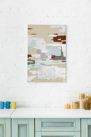 white and turquoise kitchen interior with abstract painting on brick wall