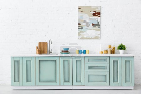 white and turquoise kitchen interior with kitchenware and abstract painting on brick wall