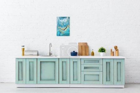 Foto de Cocina blanca y turquesa interior con menaje y pintura abstracta en la pared de ladrillo. - Imagen libre de derechos