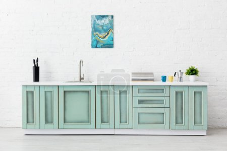 Photo pour Intérieur de cuisine blanc et turquoise avec ustensiles de cuisine et peinture abstraite sur mur de brique - image libre de droit