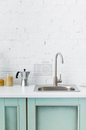 Photo pour Cuisine moderne blanche et turquoise intérieur avec ustensiles de cuisine et évier près du mur de brique - image libre de droit