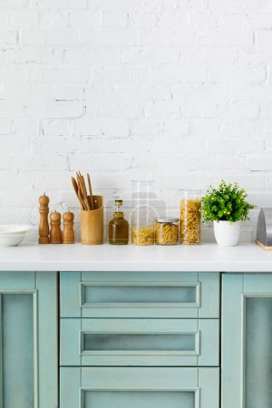 Photo for Modern white and turquoise kitchen interior with kitchenware, food containers and plant near brick wall - Royalty Free Image
