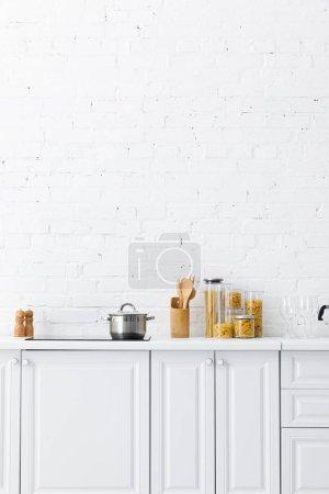 Foto de Minimalista cocina blanca moderna interior con menaje y comida cerca de la pared de ladrillo. - Imagen libre de derechos