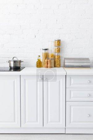 Photo pour Cuisine blanche moderne minimaliste intérieur avec plaque de cuisson à induction, nourriture, boîte à pain près du mur de brique - image libre de droit
