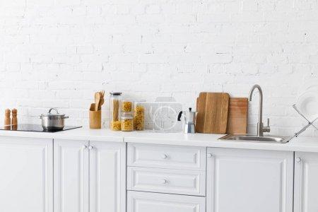 Photo pour Moderne minimaliste intérieur blanc avec ustensiles de cuisine près du mur de brique - image libre de droit