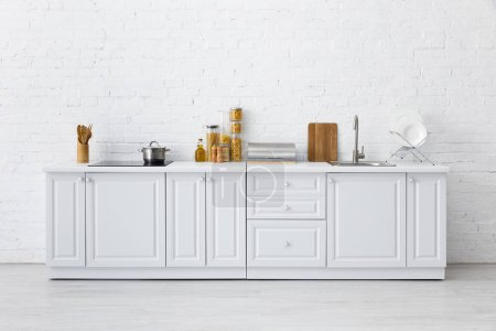 Photo for Minimalistic modern white kitchen interior with kitchenware near brick wall - Royalty Free Image