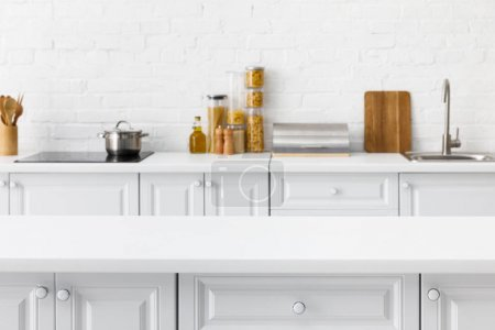 Photo for Selective focus of empty tabletop and minimalistic modern white kitchen interior with kitchenware and food near brick wall on background - Royalty Free Image