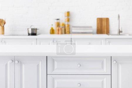 Photo pour Foyer sélectif de table vide et l'intérieur minimaliste de la cuisine blanche moderne avec la vaisselle et la nourriture près du mur de brique sur l'arrière-plan - image libre de droit