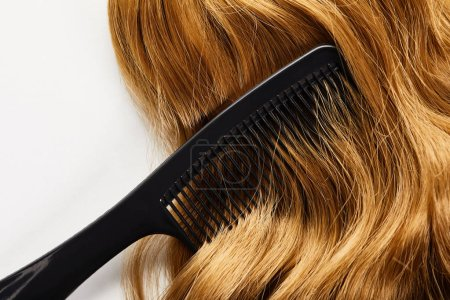 Top view of comb on brown hair isolated on white