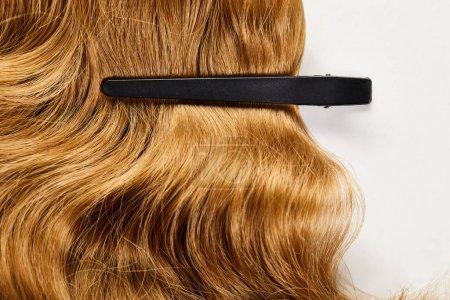 Вид сверху клипа на каштановые волосы на белом фоне