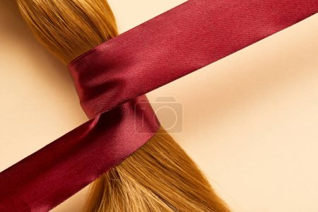 Top view of brown hair with ribbon on beige background