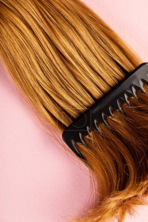 Photo pour Vue du haut des cheveux bruns et du peigne sur fond rose - image libre de droit