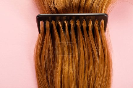 Top view of comb in brown hair on pink background
