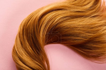 Top view of brown hair on pink background