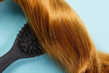 Photo pour Vue en haut des cheveux bruns brillants et de la brosse à cheveux sur fond bleu - image libre de droit