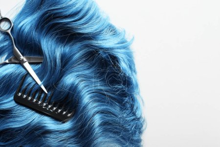 Top view of scissors and comb on wavy blue hair isolated on white