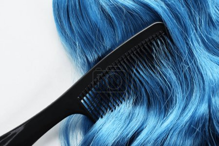 Top view of comb and blue hair isolated on white