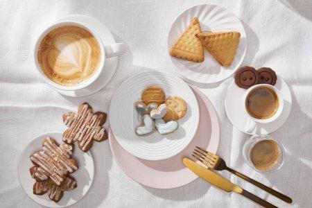 Photo pour Vue de dessus des biscuits savoureux avec glaçure et café sur nappe blanche - image libre de droit